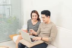 Young asian couple payment online using laptop buying movie tick Stock Images