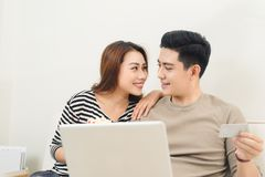 Young asian couple payment online using laptop and credit card Royalty Free Stock Photos