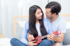 Young Asian couple playing ukulele relaxing with happiness and joyful Royalty Free Stock Photo