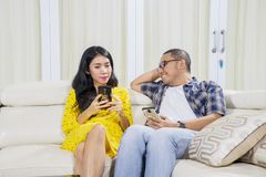 Asian couple relaxing with their phone at home royalty free stock photos