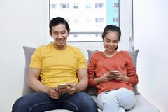 Young asian couple relaxing together with using mobile phone. On the couch Stock Photo