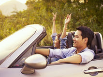 Young asian couple riding in a convertible car. Young asian couple riding in a convertible sport car enjoying the cool breeze at sunset Royalty Free Stock Image