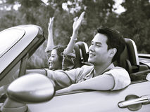 Young asian couple riding in a convertible car Royalty Free Stock Photo