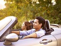 Young asian couple riding in a convertible car Stock Photos