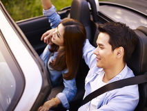 Young asian couple riding in a convertible car Royalty Free Stock Image