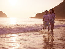 Young asian couple running on beach. Happy young asian couple running on beach in during sunset or sunrise Royalty Free Stock Images