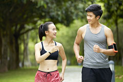 Young asian couple running jogging in a park stock photo