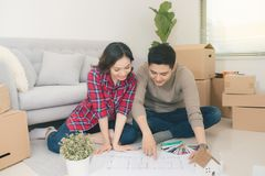 Young asian couple sitting on the floor and looking at the blueprint of new home. stock photography