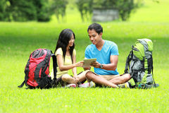 Young asian couple sitting on the park looking a tablet pc Stock Photos