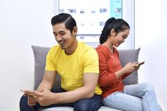 Young asian couple sitting on the sofa with mobile phone royalty free stock photo