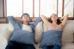 Young asian couple smile relax comfortable on sofa in the living room in holiday, family leisure and resting with happy. In vacation on couch at home, lifestyle royalty free stock image
