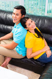 Young Asian couple on sofa or couch Royalty Free Stock Photos