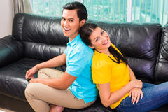 Young Asian couple on sofa or couch Stock Image