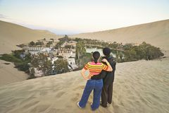 A young asian couple stand on the desert and enjoy the view of Huacachina, Ica, Peru. stock photography