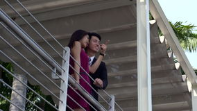 Young asian couple standing and chatting on balcony stock video footage