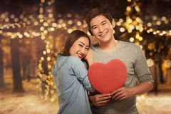 Young asian couple standing in embrace and holding heart shape Royalty Free Stock Images