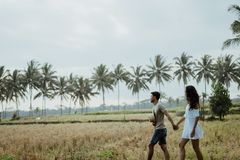 Couple stylish walking in rice field together stock photos
