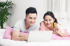 Young asian couple surfing on internet and shopping with laptop Stock Images