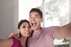 Young asian couple taking selfie photo with big windows interior Stock Photo