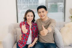 Young asian couple with thumbs up in new home.  Royalty Free Stock Image