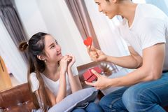 Young asian couple together, man holding surprise stock image
