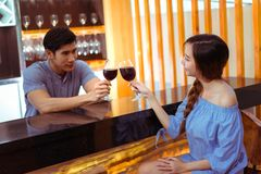 Young asian couple together man and woman clink glasses. Young asian couple together men and women clink glasses drink wine, cocktail in bar luxury party Stock Images