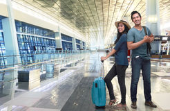 Young asian couple tourist with luggage waiting flight Royalty Free Stock Photos