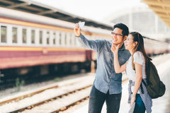 Young Asian couple traveler taking selfie together using smartphone waiting for trip at train station platform in Asia. Backpack travel, Love relationship Royalty Free Stock Images