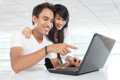 Young Asian couple watching on a laptop, smiling Stock Photography
