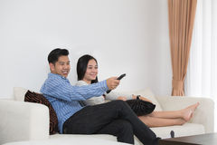 Young Asian couple watching television Royalty Free Stock Images