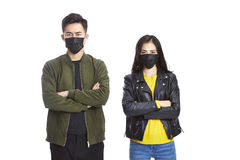 Young asian couple wearing black mask. Young asian men and women wearing black mask looking at camera frowning, isolated on white background Royalty Free Stock Photo