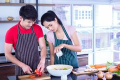 Young, Asian Couples  in apron, make cooking salad for food together. In kitchen at home with full of ingredient on table. Couples concept royalty free stock photography