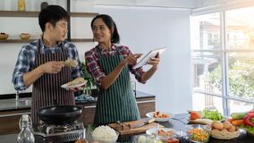 Young Asian couples are happy to cook together, two families are helping each other prepare to cook in the kitchen royalty free stock image