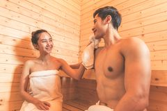 Young Asian couples or lovers have romantic relaxing in sauna ro. Om. Skin care heat treatment and body clean up and refreshing in spa with steam bath. Healthy Royalty Free Stock Photos