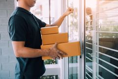 Young asian courier is using the hand of the knock at the door to deliver the goods.  royalty free stock photo