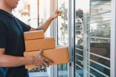 Young asian courier is using the hand of the knock at the door to deliver the goods stock images