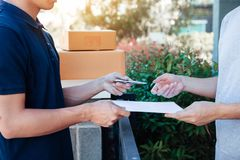 Young asian delivery staff holding the pen and documents submitting giving to the customer receiving the parcel at front house royalty free stock image