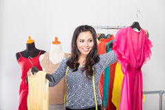 Young asian designer comparing two dresses in her hands, smiling Stock Photos