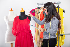 Young asian designer hold fabric enrobing it to the mannequin, s Royalty Free Stock Image