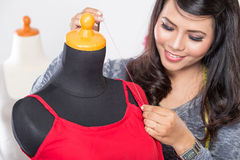 Young asian designer sewing a fabric on a mannequin, close up Stock Image