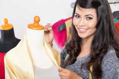 Young asian designer sewing a fabric on a mannequin, smiling to Stock Image