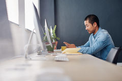 Young Asian designer using a cellphone at his office desk Royalty Free Stock Photography