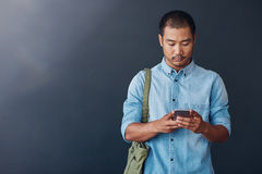 Young Asian designer using a cellphone in a modern office. Casually dressed young Asian designer reading a text message on his cellphone while standing against a royalty free stock photography