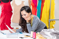 Young asian designer woman using a laptop and smiling,clothes ha Royalty Free Stock Image