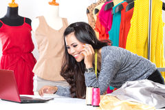 Young asian designer woman using a laptop and smiling,clothes ha Stock Photography