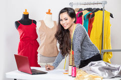 Young asian designer woman using a laptop and smiling,clothes ha Royalty Free Stock Photos