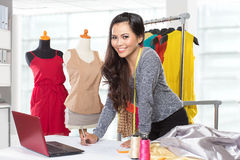 Young asian designer woman using a laptop and smiling,clothes ha Stock Photos