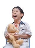 Young Asian doctor boy playing and curing bear toy Royalty Free Stock Photography