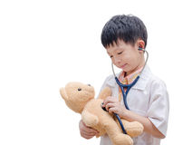 Young Asian doctor boy playing and curing bear toy Stock Photo