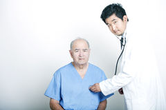 A young Asian Doctor comforting a Senior adult patient Royalty Free Stock Images
